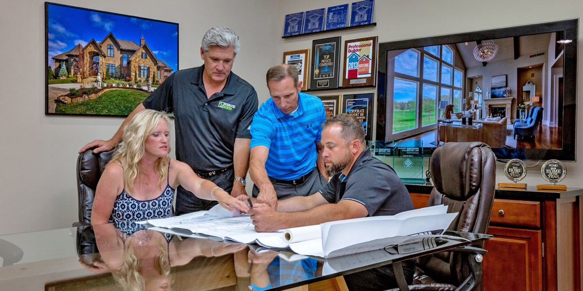 Custom home builder reviewing plans with home buyers